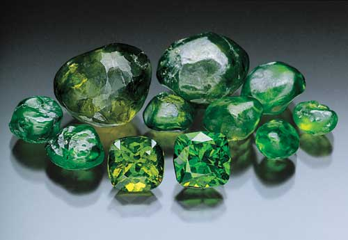 Rough and cut demantoid garnets